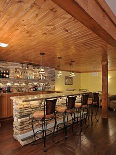 Basement Bar Stonework. A wood plank ceiling, hardwood floors and natural stonework set a rustic, outdoors tone for this basement-turned-ski lodge. A fully stocked bar and lounge area makes this the perfect place to relax after hitting the slopes or for watching sports on the weekends.