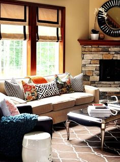 Mix of pillows; rug; shades, furniture placement with a corner fireplace