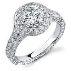 Features a halo of pave-set round diamonds around the center stone. In addition, this ring also features pave-set round diamonds across the top-half. From the side view, we have accented the top-half of pave-set diamonds, while the entire bottom-half of the ring has hand-engraved scroll accents.