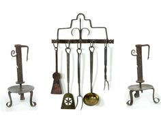 "WROUGHT IRON RACK WITH UTENSILS.   American, 19th and 20th century. Rack with hooks, 15""l., and three utensils with brass parts signed ""T. Loose"". Together with an earlier spatula, two-prong fork, and pair of wrought iron candlesticks with side push ups, 11 1/2""h."