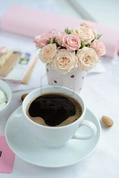 cup of coffee and a bouquet of delicate pink roses on the table in the morning Stock Photo