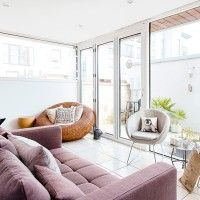Bright garden room with mauve sofa and woven seat