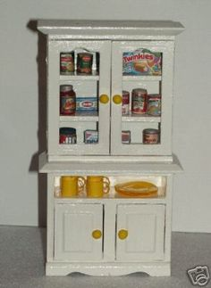 www.DollysGallery.com  Dollhouse Miniature Kitchen Cabinet filled with cereal, chips, peanut butter, crackers, canned foods, spaghetti sauce, noodles, twinkies, plates & cups.   DollysGalleryMinis can be found on FB,  Dolly's Gallery is on Ebay and Etsy   1:12