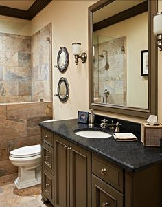 "This bathroom feels a little more masculine, which is perfect for this basement. Countertop is Soapstone oiled"". Shower and floor is a porcelain tile to look like slate from Crossville Tile. The tile size is a 12″ x 24″."