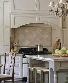 French-Style Kitchen Backsplash ~ This French-style kitchen is the perfect setting for the tile backsplash. Detailed tiles add a personal touch while exuding quiet confidence. The sandy colors add continuity while avoiding monotony. Tucked quaintly above the range, the backsplash is a beautiful tribute to the traditional French style of the kitchen