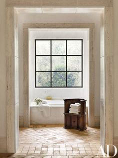 A 17th-century Italian walnut throne chair meets antique terra-cotta flooring in the master bath   archdigest.com