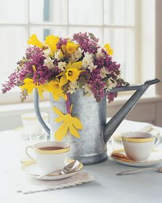 Do this for porch with bronze can and hydrangeas. A watering can holding cut spring blossoms will continue to nurture flowers long after the