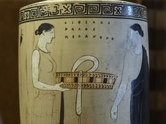 To Diphilos the awesome son of Melanopos - II  A woman and her maid are standing one in front of the other. The maid wears a sleeveless chiton; her hands hold a flat basket containing sashes; the other woman wears a black himation over a long-sleeved chiton. The right hand is lowered along her hip; the left arm is folded and hidden under the himation. The painter has painted a walking blackbird between the two women. Oinochai and sashes are suspended on the walls. At center the inscription…