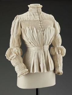 Woman's ivory silk blouse with high necked self ruffled released pleat collar with interior braid, peplum waistband, and set in Elizabethan shaped sleeves with graduated puffs stitched down by narrow rows of smocking stitches, by Liberty & Co.,  English, c. 1890s.