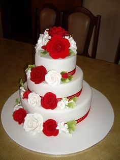 - 3 tier wedding cake with red and white sugar roses on all tiers
