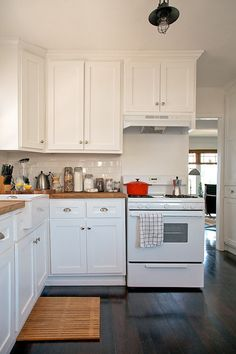 white cabinets, butcher block counters, dark wood floors