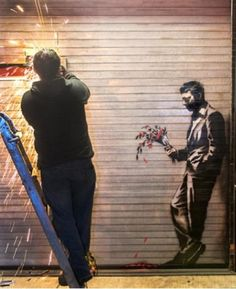 "Banksy's ""waiting in vain"" is being cut from the rolling shutter door of the Hustler club. NYC"