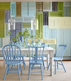I love this! LOVE the shutter wall in multi-color and the color palette. Love the white table and mismatched chairs in the same blue color.