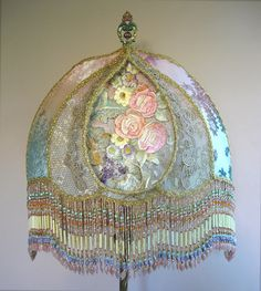 Pretty antique floor lamp holds a custom Teardrop Shadowbox shade filled with exceptional Victorian embroidered flowers in delectable pastel colors. Other panels are covered in vintage silk cut velvet, metallic lace and antique gold net from France. Hand beaded fringe in pastel tones include rare vintage bugle beads. Lights up beautifully.