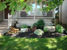 Beautiful small garden with Armour stone, shrubs, and black mulch.
