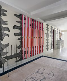 The entry features a bronze bench by Robert Wilson, a wall sculpture by Rana Begum, and a vintage Pablo Picasso rug; the hand-painted wallpaper is by Porter Teleo.   - ELLEDecor.com