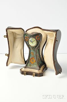 Eugene Feuillatre, Art Nouveau Table clock Plique-a-Jour Enamel. The yellow enamel dial with green Arabic numeral indicators and two butterflies within a shaped silver-gilt case with plique-a-jour enamel floral and foliate motifs, the case with conforming flowers and foliage, key-wind brass movement signed and numbered Lepine, 28957, H:. 6 1/2 in. French maker's mark and guarantee stamps, signed, in original fitted case.