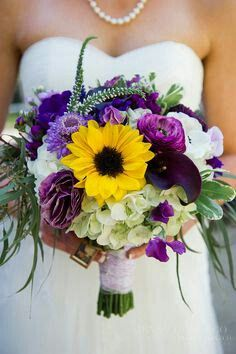 Lovely Wedding Bouquet Arranged With: White Jumbo Hydrangea, White Veronica, Purple Calla Lilies, Purple Lisianthus, Violet Ranunculus, Lavender Scabiosa, Yellow Sunflowers + Several Varieties Of Greenery & Foliage