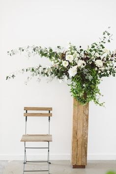 Tall unfinished wood pedestal for sprawling white flowers and greenery by Sarah Winward
