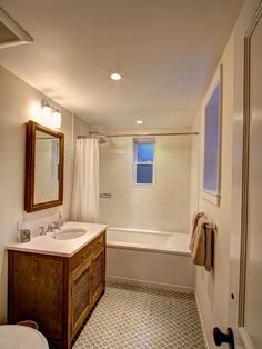 The main floor bathroom is similar to the master, though its light colors give it a more casual feel and reflect the oak paneling in the office niche.