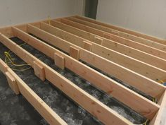 Build your riser with a perimeter of 2x12s but save money and run 2x8s (or 10s) with mid span supports for the internal joists.