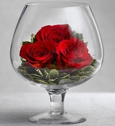 Passionate red roses are distilled on a bed of fresh greenery in this truly original, romantic arrangement. Designed by hand inside an oversized clear glass brandy snifter, this luxurious Happy Hour bouquet will wow your Valentine all day long. Glass Centerpieces, Wedding Centerpieces, Wedding Table, Centrepieces, Rosen Arrangements, Floral Arrangements, Blossoms Florist, Deco Nature, Decoration Plante