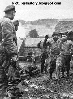 """Officers of the 1st SS Division """"Leibstandarte Adolf Hitler"""" Sturmbannführer Josef Diefenthal and Sturmbannführer Gustav Knittel look at the prisoners, 3rd Battalion, 119th Infantry Regiment, 30th Infantry Division of the American in a street at the Belgian town of Stoumont. Ardennes, December 16, 1944."""