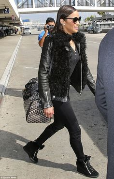 Travelling light: The 38-year-old carried just a small black and white patterned bag which complemented her all-black outfit, consisting of ...