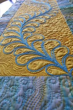Montana Gold at MarveLes Art Studios.  Gold silk yarn in a feather motif with additional free motion quilted swirls in yellow thread