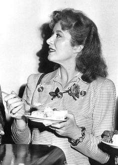 1940s photo. Greer Garson enjoying a piece of cake. Notice rose threaded through her front button.