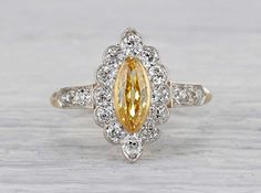 Antique Edwardian engagement ring made in 18k yellow gold and platinum. Centered with a GIA certified .42 carat fancy vivid orange yellow marquise cut diamond. Accented with old European cut diamonds. Circa 1915.