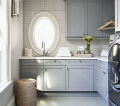 L shaped laundry room features gray shaker cabinets paired with white quartz countertop and gray mosaic tiled by Walker Zanger.
