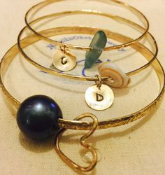 Custom Bangles. The perfect gift of serenity with a personalized touch. Handcrafted gold filled and silver bangles with your choice of shells and pearls. Personalized name plates and charms.