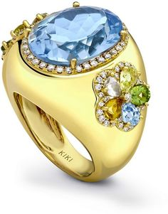 This stunning statement ring features a beautiful blue topaz centre stone set either side with delicate multi gemmed petals in 18ct yellow gold.