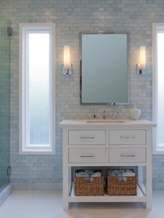A white porcelain tile floor and iridescent tile walls create a luxurious all-white bathroom. Soft sconce lighting and a white wood vanity contribute to the airy feel of the space.