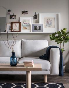 MOSSLANDA Bilderleiste in Weiß über einem Sofa. Darauf sind Fotos und Kunstwerke zu sehen. Kleinere Fotos wurden mit Dekoklebestreifen befestigt.