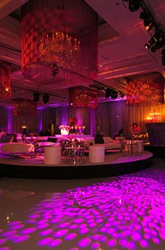 The vibrant circular patterns of pink gobo lights create patterns of countless O's along the dance floor.