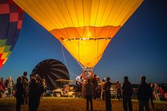 Crowds watch some pilots inflate their balloon during the glow event Saturday evening at Balloon Fiesta Park.<br />