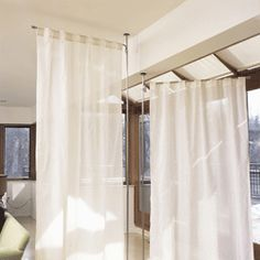stand-alone curtain panel holders- floor to ceiling tension mount pole holds it in place anywhere. from Umbra