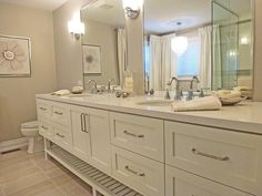 """Sleek and sophisticated, this custom vanity is stocked with storage options. Designer Tracy Black designed this elegant, oversized piece, which measures an eye-catching nine feet long and 25 inches deep. """"A vanity is so much more practical and functional with deep drawers instead of just doors,"""" she says. The roomy drawers and center cabinets easily accommodate bath and beauty products, hair-styling tools and more. The lower open shelf is a practical spot for storing towels or baskets and…"""