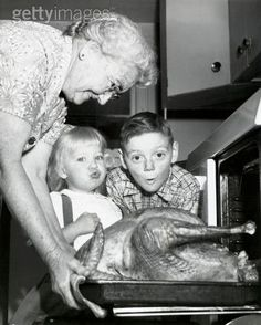 Vintage photo Looks like  Grandma is taking the Thanksgiving turkey out of the oven while the grandchildren watch. Fresh Farmhouse