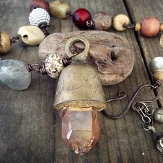 A large mystic coated peach quartz point set into an old Indian brass bell on a necklace of large and beautiful wire wrapped rustic tribal beads (faceted quartz, tumbled stone, African cast brass and silver and stone) in neutral colors.