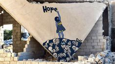 A 22-year-old-rebel artist's street art in Syria: Girl writing hope painted on rubble.