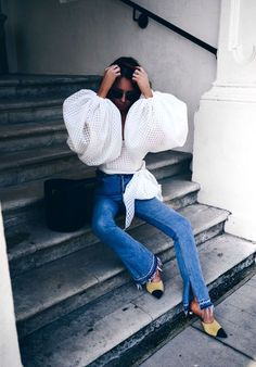 White blouse with oversized statement sleeves, flare jeans, and heels. | They All Hate Us