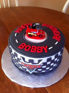 8 inch cake covered in fondant, all caaents are fondant, Cars logo in front is EI, Car is candle TFL