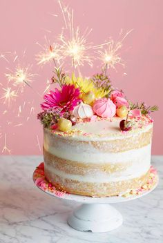 The Ultimate Naked Birthday Cake from www.whatsgabycooking.com Layers of homemade cake, lemon curd, crumbled meringue cookies, swiss buttercream frosting and sparklers to boot!! (@whatsgabycookin)