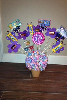 A friend made this for an 18th birthday gift. The butterflies and flowers were die cuts. She attached everything to wooden dowels. She also used a styrofoam ball which she got glued into the pot for the bouquet of lollipops.