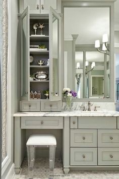 Sophisticated Bathroom Features Gray Vanity Cabinets Paired With A Statuary Marble Countertop Lucite Stool Is Tucked Under Topped Mirrored