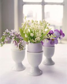 Grouped together, these make a lovely springtime centerpiece. Individually, they make a pretty marker for place settings. Break an egg at the top of its shell, drain the contents, and carefully rinse out the inside. Here, a trio of eggs are bursting from the crack with small buds of lilacs, lily of the valley, and violas.