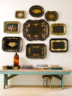 A collection of Toleware (a style of hand-painted tin popular in the U.S. during the 18th century) is hung on the wall to create a stunning art installation.